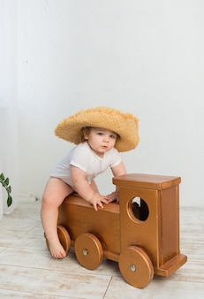 Little girl in a white bodysuit and a straw hat sits on a wooden locomotive on a white room