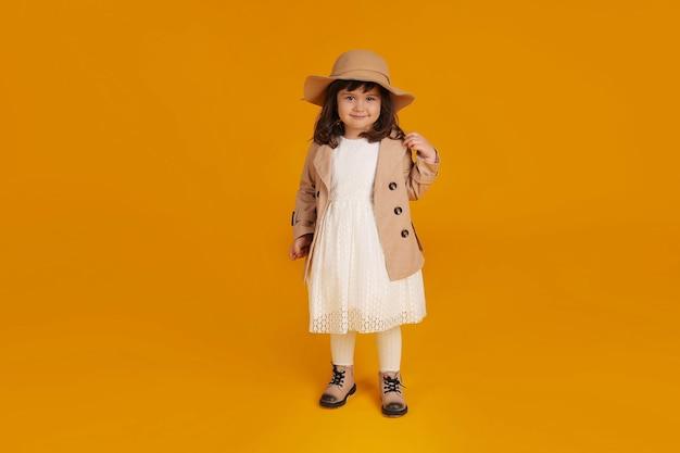 Маленькая девочка белое платье бежевый плащ бежевая шапка бежевые сапоги желтый фон