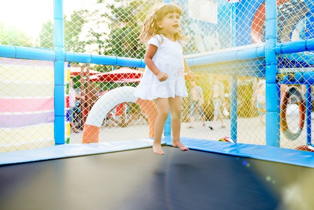 Little girl in white dress jumps on trampoline. photo of child in full growth in jump