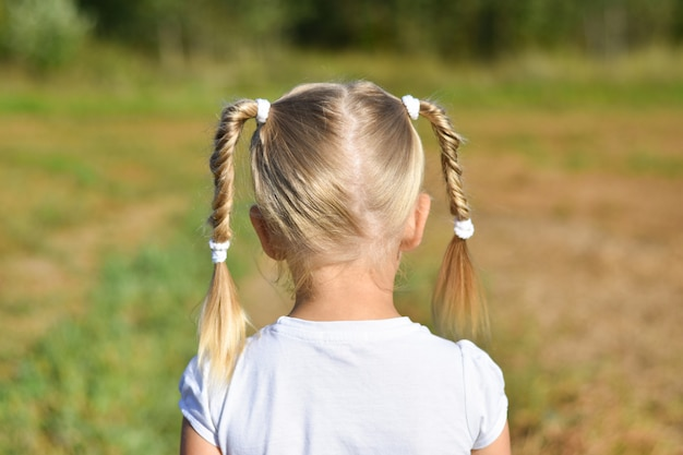 Little girl in white dress looks forward in the field, rear view, close-up