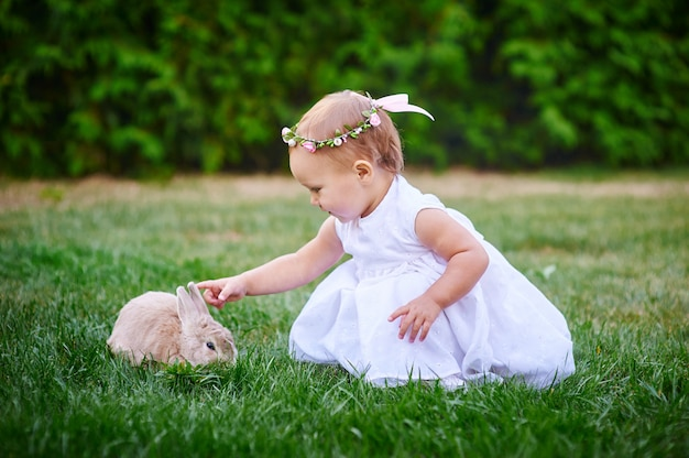Little girl in a white dress plays with a rabbit in the park