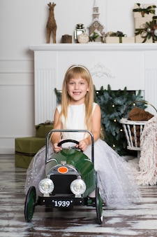 Little girl in a white dress rides a vintage children's car in christmas decorations
