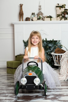 Little girl in a white dress rides a vintage children's car.