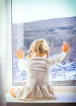 A little girl in a white dress sits by the window and looks at the winter forest