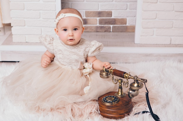 A little girl in a white dress sitting by the fireplace next to an old phone