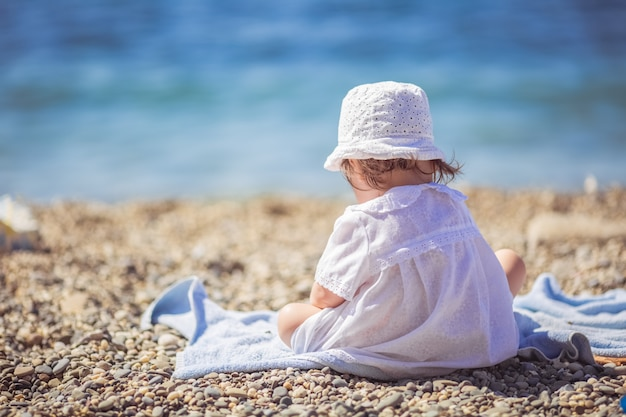 Little girl in white dress sitting by the sea. the girl enjoys the beauty of the sea.