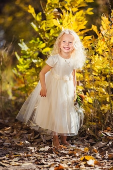 A little girl in white dress who smiles on a background of yellow leaves