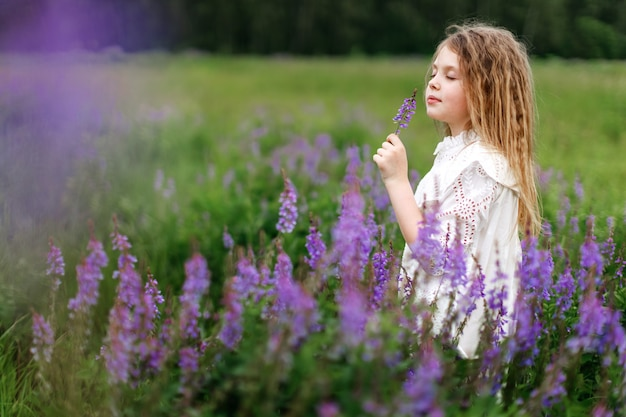 A little girl in a white dress with beautiful flowers in the field in summer
