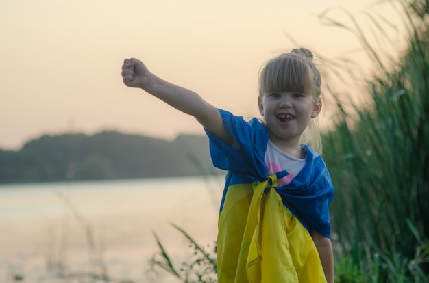 Little girl in a white dress with a yellow-blue flag of ukraine