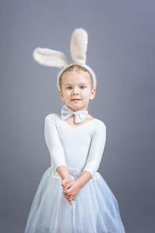 Little girl in white easter bunny costume on gray