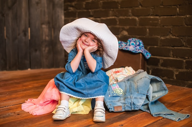 Little girl in white hat sitting in suitcase with things and look at the camera