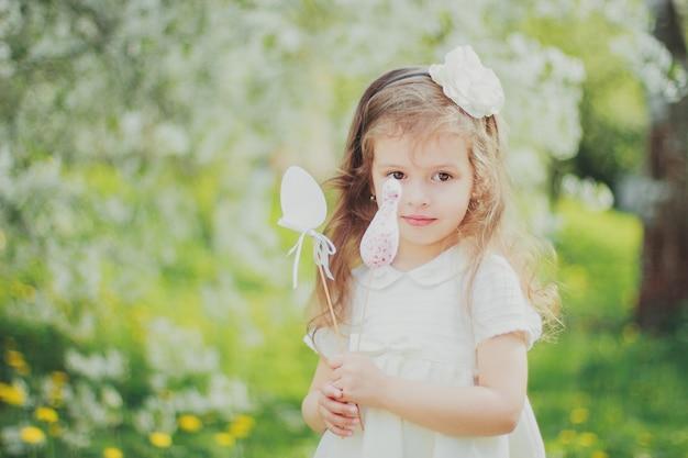Little girl in white hold easter toy eggs on sticks in the spring cherry garden