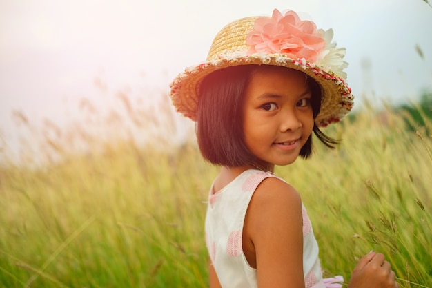 Little girl in white lace shirt wear straw hat and necklace is feeling relaxed.