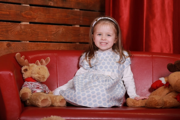 Little girl in white polka dots dress having fun on the red couch in the christmas studio. christmas tree, teddy bear and gifts box on the front of.