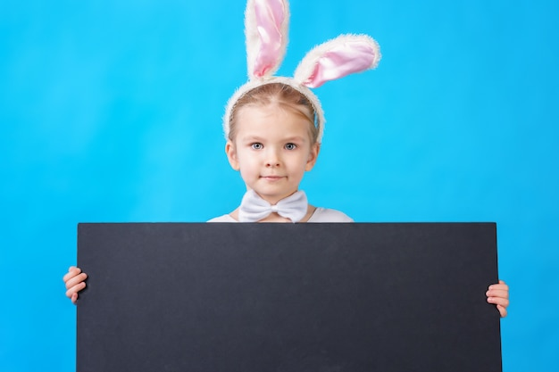 Little girl in a white rabbit costume with blank placard or poster