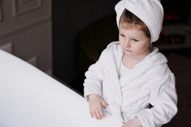 Little girl in a white robe after taking a bath