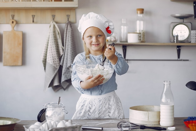 Little girl in a white shef hat cook the dough for cookies