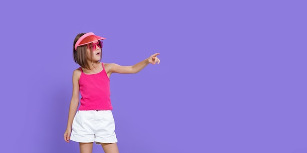 A little girl in white shorts, a pink t-shirt, pink trendy glasses and a summer visor