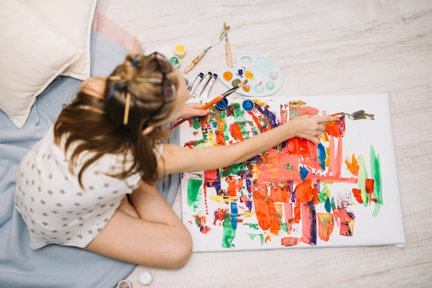 Little girl in white sitting on floor and painting with gouache on canvas