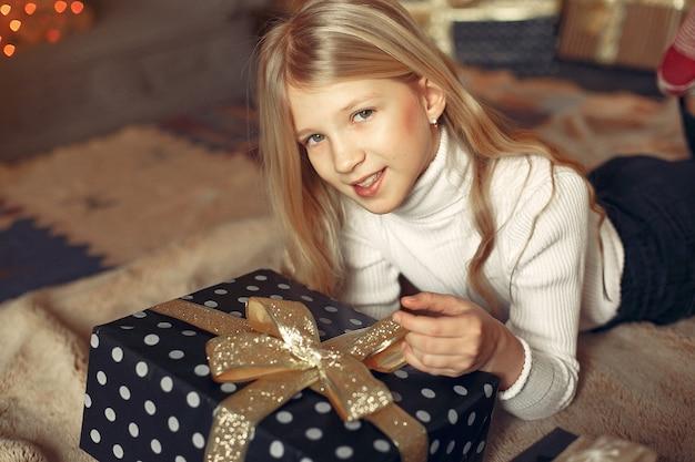 Bambina in un maglione bianco vicino all'albero di natale con il presente