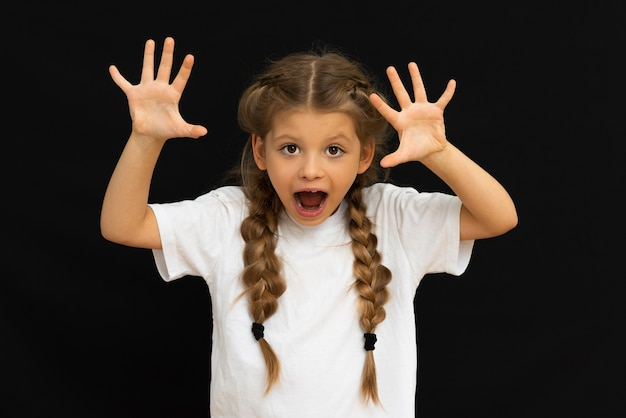 A little girl in a white t-shirt on a black background.