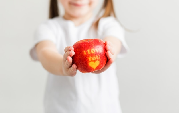 A little girl in a white t-shirt holds an apple in her hands with the inscription i love you. vertical photo