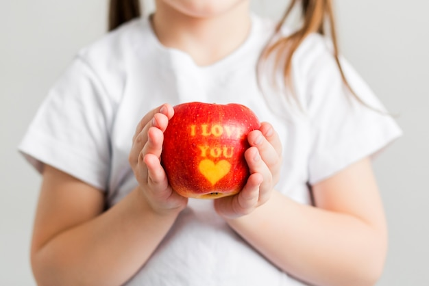 A little girl in a white t-shirt holds an apple in her hands with the inscription i love you. vetical photo