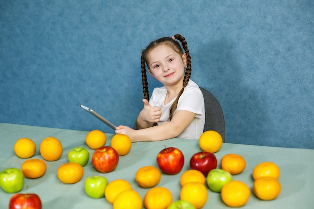 Little girl in a white t-shirt holds a tablet in her hands and studies the fruits