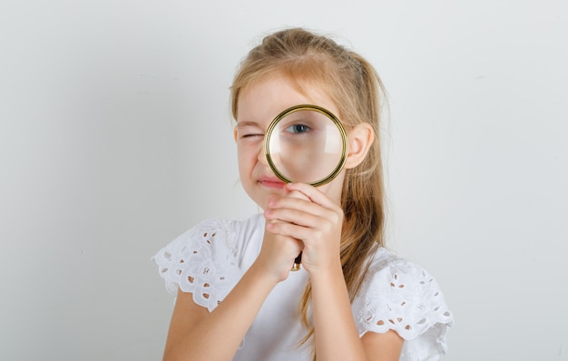 Little girl in white t-shirt looking through magnifying glass