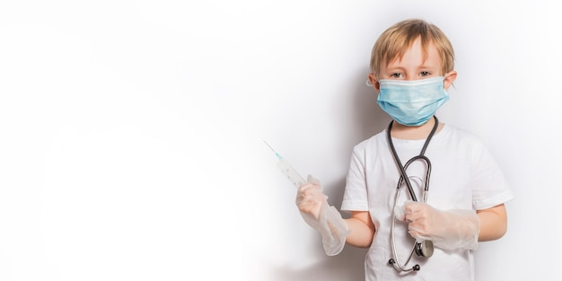 Little girl in a white t-shirt and a medical mask playing doctor holding a syringe