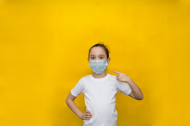 Little girl in a white t-shirt and protective mask points her finger at the mask. protection against coronavirus