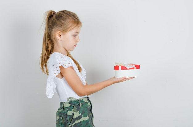 Little girl in white t-shirt, skirt giving someone gift box and looking careful