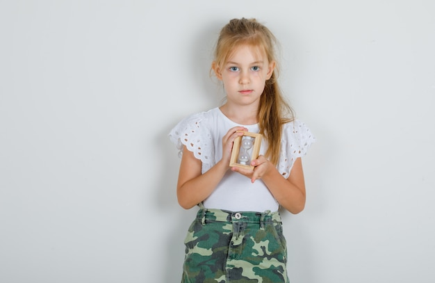 Little girl in white t-shirt, skirt holding hourglass and looking careful