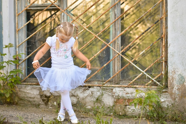 A little girl in a white t-shirt and skirt learns to dance on the street near the window of an old house