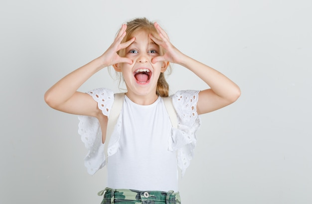 Little girl in white t-shirt, skirt opening eyes with fingers and looking funny