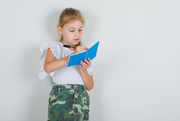 Bambina in maglietta bianca, gonna che prende appunti sul quaderno e sembra occupata