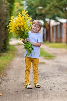 A little girl in a white t-shirt and yellow jeans stands on a country road in the village and holds a bouquet of yellow autumn flowers in her hands and smiles.