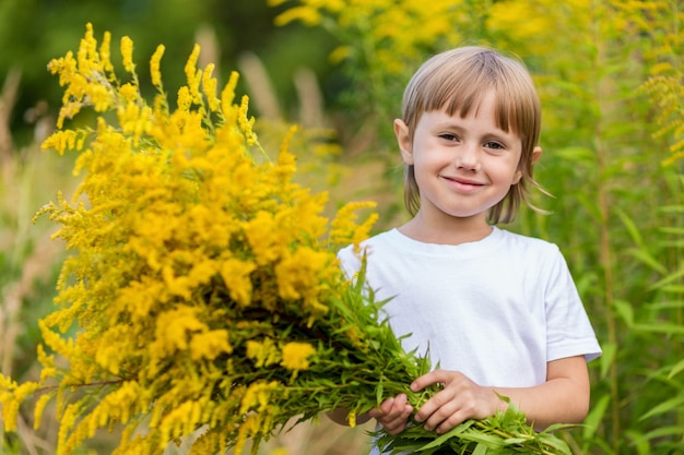 A little girl in a white t-shirt and yellow jeans stands in the flower field and holds a bouquet of yellow autumn flowers in her hands and smiles.