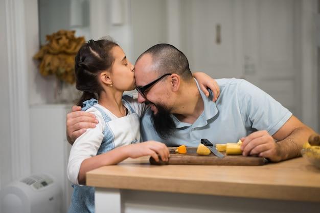 Маленькая девочка, которая готовит с любящим заботливым отцом на современной кухне. счастливый молодой отец с милой дочерью на кухне.