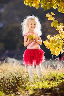 A little girl who smiles on a background of yellow leaves