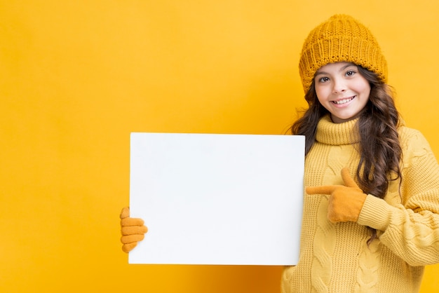 Little girl in winter clothes holding paper sheet