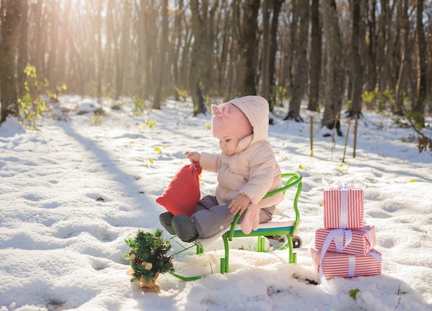 Little girl in winter clothes sitting in a sled with gifts in the winter forest