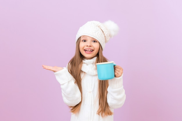 A little girl in a winter hat is holding a cup with a drink and the other is pointing to the side.