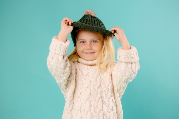Little girl in winter hat and sweater on blue