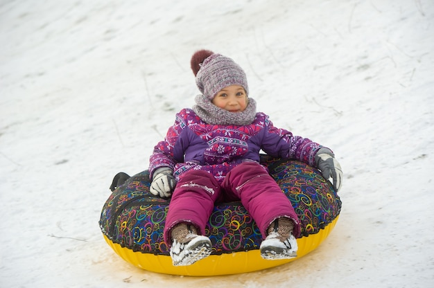 A little girl in winter in purple clothes and an inflatable circle rides down the hill on the street