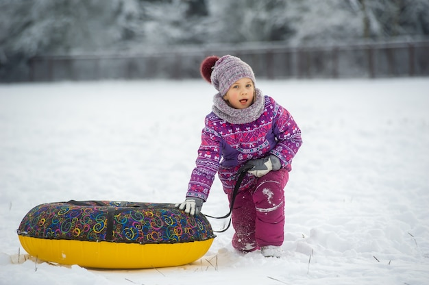 A little girl in winter in purple clothes and an inflatable circle walks on the street in a snow-covered forest