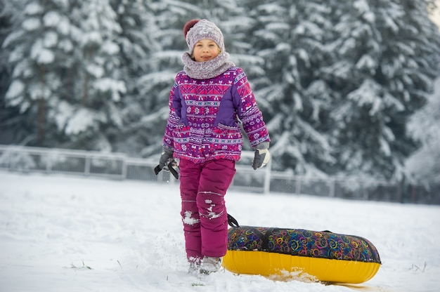 A little girl in winter in purple clothes and an inflatable circle walks on the street in a snow-covered forest.