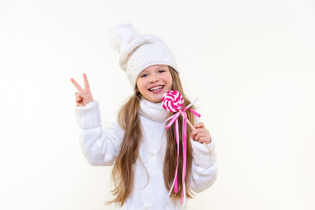 A little girl in a winter sweater and hat holds a delicious lollipop and smiles on a white isolated background.