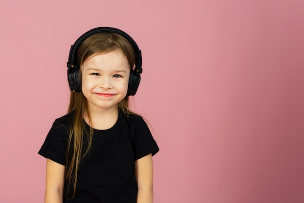 A little girl in wireless big black headphones. the concept of listening and enjoying music. place for text, copyspace