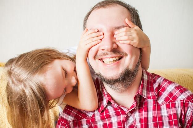 Маленькая девочка желает папе счастливого дня отца. дочь обнимает папу, закрывает глаза руками